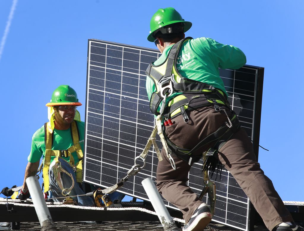 Workers install solar paneling.