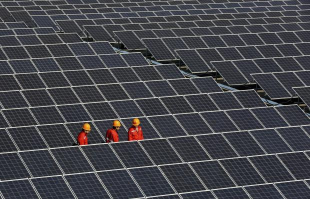 Workers walk among newly installed solar panels at a solar power plant in Zhouquan township of Tongxiang, Zhejiang province December 18, 2014. A new report highlights the co-benefits of renewable energy sector. REUTERS/Stringer