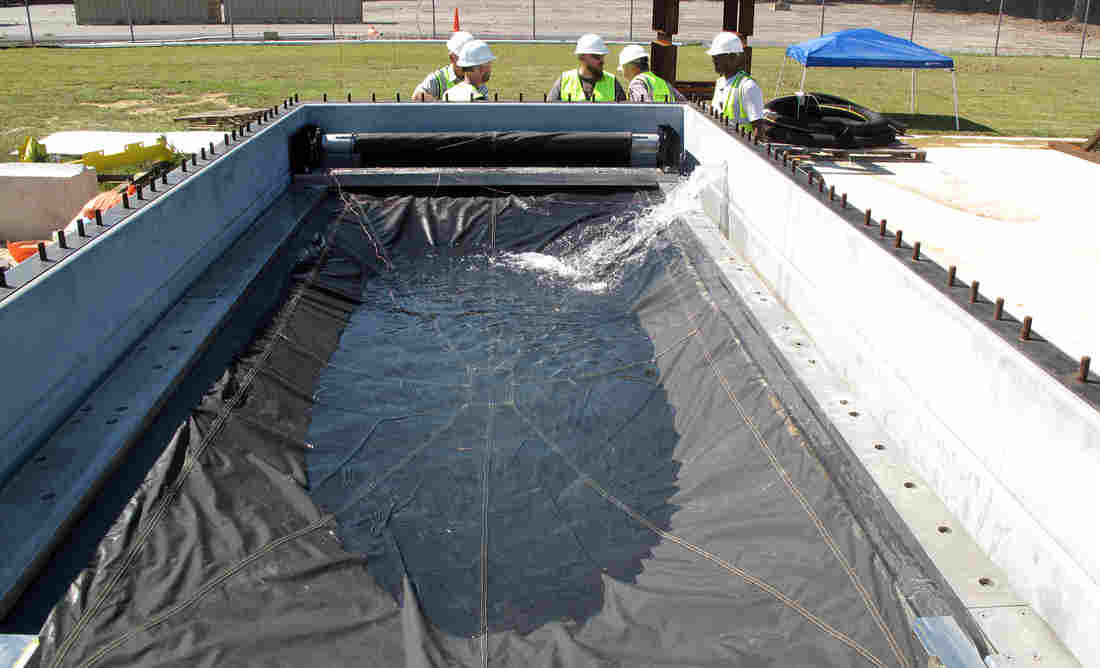Engineers test the Flex-Gate, a big sheet of waterproof fabric designed to cover subway entrances and keep water out. Its creation was inspired in part by roll-up metal doors used to cover store entrances. Joel Rose/NPR